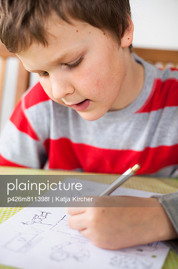 Elementary boy drawing in book at table