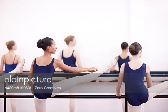 Group of teenage ballerinas practicing at the barre