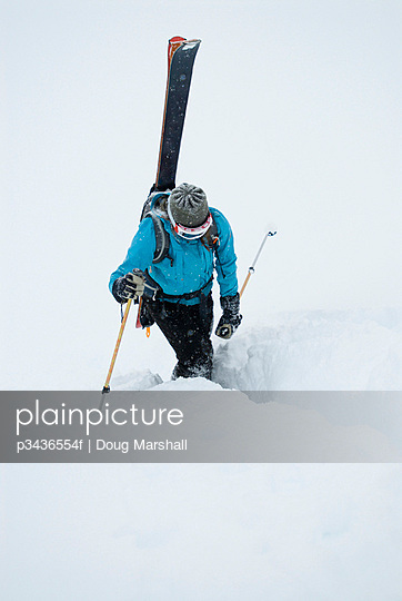 A young woman packs her skis and kick steps up a section of trail in the backcountry of the Canadian Rockies