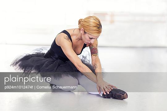 Ballet dancer stretching leg in studio