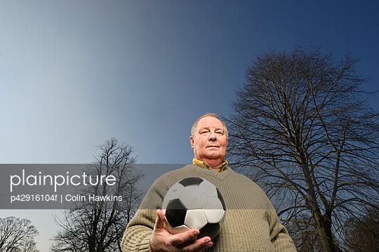 Older man carrying soccer ball