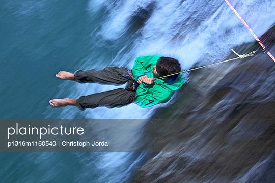 Junger Mann ruht sich aus nachdem er es nicht geschafft hat auf einer Highline über einen Fluss zu balancieren, Füssen, Bayern, Deutschland, Europa - p1316m1160540 von Christoph Jorda