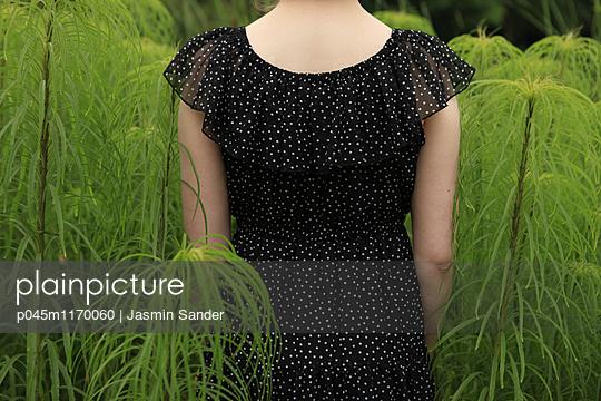 Frau steht zwischen Gräsern - p045m1170060 von Jasmin Sander