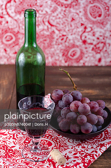 Red wine, wine glass and wine grapes on wooden table