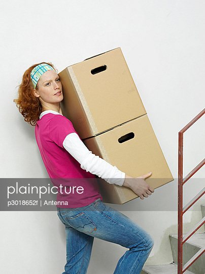 A woman carrying boxes up stairs