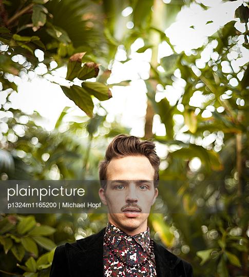 Porträt eines jungen Mannes im Grünen - p1324m1165200 von michaelhopf