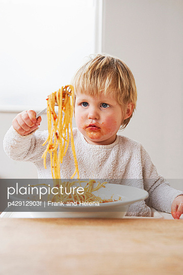 Messy baby boy eating spaghetti