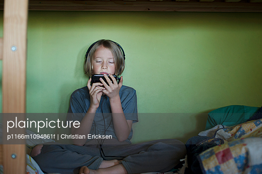 Front view of boy using smart phone while sitting on bed