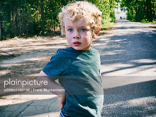 Kleiner Junge blickt neugierig - p358m1160198 von Frank Muckenheim