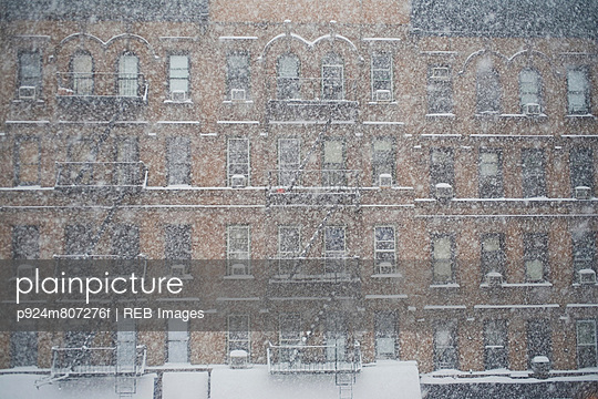 Snow falling by apartment buildings