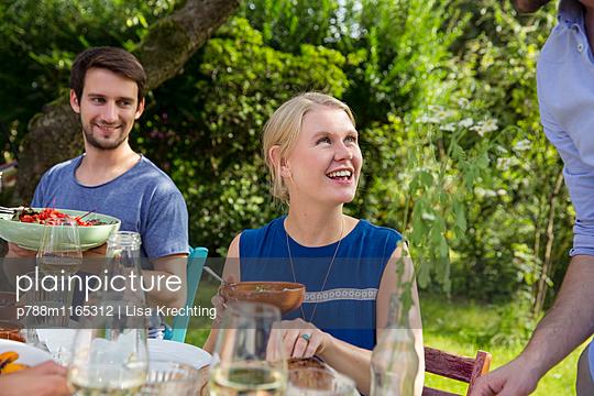 Freunde beim Essen im Garten - p788m1165312 von Lisa Krechting