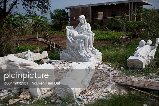 Catholic statues strewn around outside of a factory, in Nam Dinh, Vietnam, Southeast Asia
