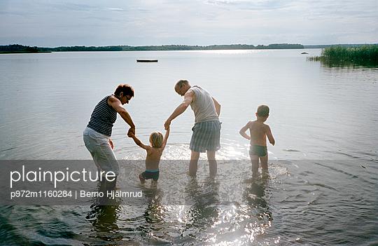 Enkel und Großeltern am Seeufer - p972m1160284 von Berno Hjälmrud