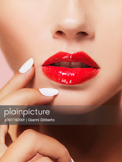 A woman\'s lips with bright red lipstick, close-up of mouth