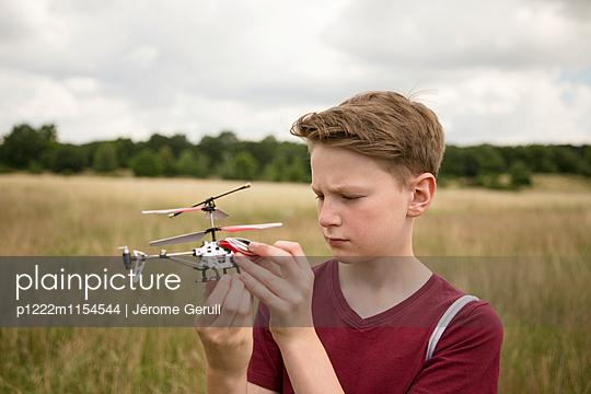 Junge mit Spielzeughubschrauber - p1222m1154544 von Jérome Gerull