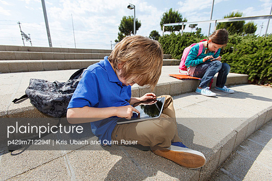 Boy using tablet computer outdoors