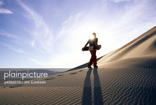 Man walking up sand dune with snowboard | Stock Images Page