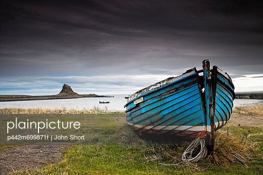 A Weathered Boat Sitting On The Shore With Lindisfarne Castle In The Distance; Lindisfarne Northumberland England