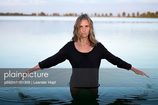 Frau steht im Wasser und streckt die Arme aus - p552m1161309 von Leander Hopf