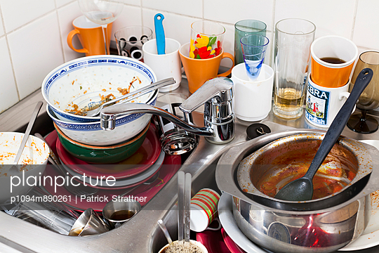 Stacks of dirty dishes in a domestic kitchen sink
