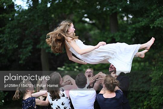 Junge Leute werfen Freundin in die Luft - p1258m1154701 von Peter Hamel
