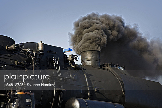 Part of a steam locomotive. From the funnel a lot of dark smoke. Germany.