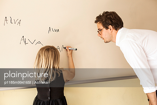 Male teacher watching girl practicing her name on whiteboard
