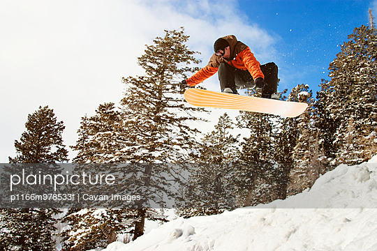 Man Snowboarding over Jump