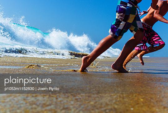 Boys playing in surf at beach - p1053m1152830 von Joern Rynio