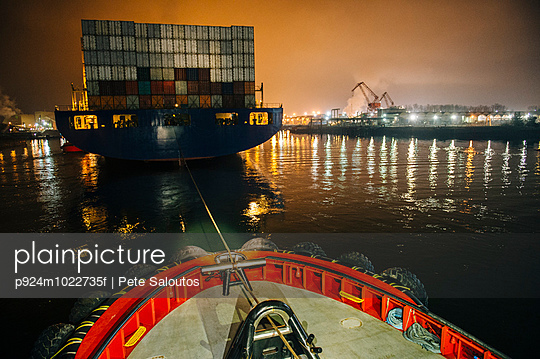 Tugboat manoeuvring cargo ship in harbor at night, Tacoma, Washington, USA