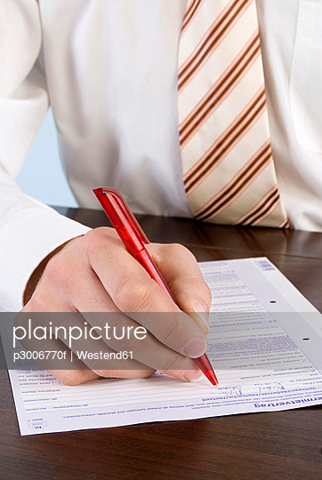Businessman filling in application form, close-up, mid section