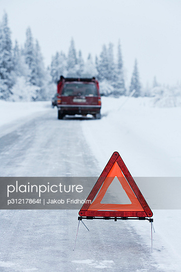 A warning triangle on a country road in the winter Sweden.