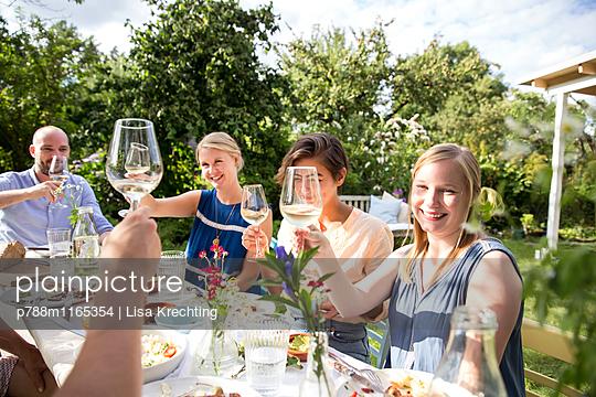 Freunde stoßen an mit Weißwein  - p788m1165354 von Lisa Krechting