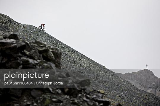 Mountainbiker fährt eine Geröllhalde in den Bergen hinunter, Ischgl, Tirol, Österreich - p1316m1160404 von Christoph Jorda