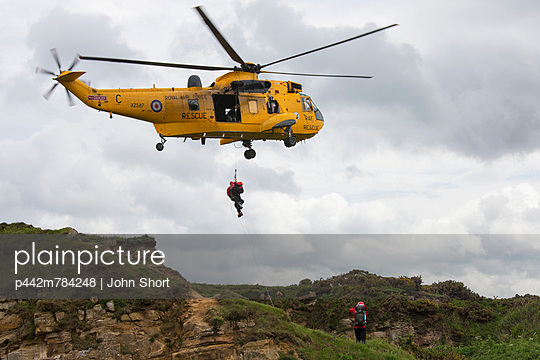 Rescue Workers Hang From A Helicopter In Mid-Air; Northumberland England