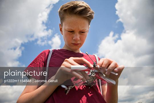 Junge mit Spielzeughubschrauber - p1222m1154548 von Jérome Gerull