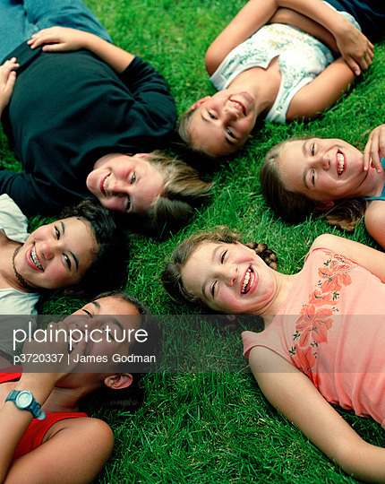 Group of six girls laying on grass
