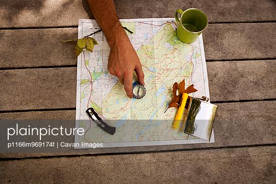 Hand, Compass, Whisky Flask, and Mug on Trail Map
