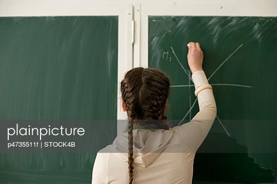Teenage girl writing on blackboard