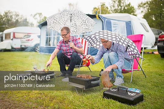 Men barbecuing in rain