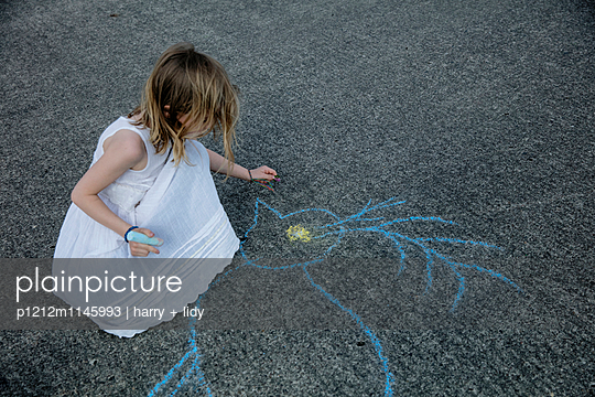 Mädchen malt mit Straßenkreide einen Vogel auf den Asphalt - p1212m1145993 von harry + lidy