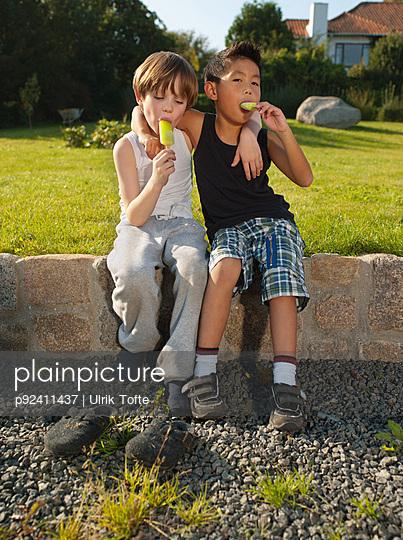 Boys sitting on wall and enjoying ice loliies, portrait