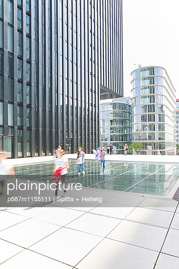Passanten gehen an modernen Bürohäusern vorbei - p587m1155111 von Spitta + Hellwig
