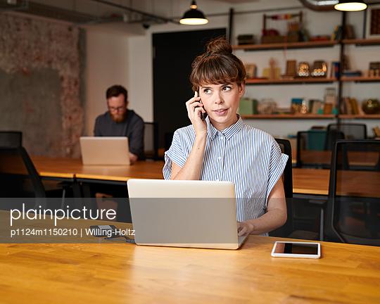 Junge Frau telefoniert am Arbeitsplatz - p1124m1150210 von Willing-Holtz