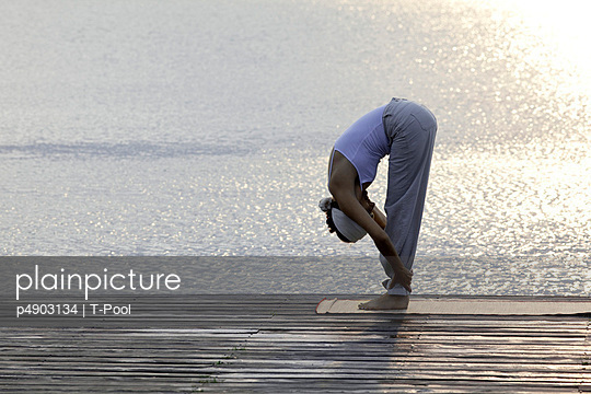 Woman doing yoga exercise on a jetty at a lake