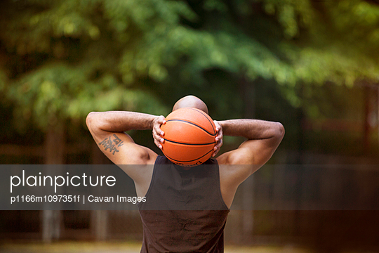 Rear view of basketball player holding ball behind head