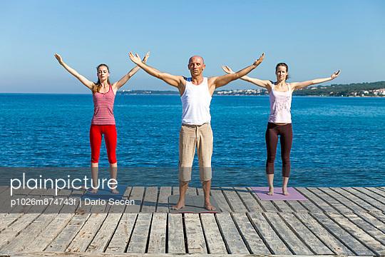 People practising yoga on a boardwalk