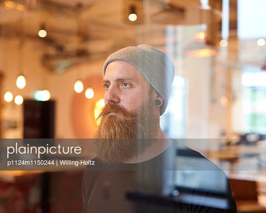 Mann mit Bart und Mütze hinter einer Glasscheibe - p1124m1150244 von Willing-Holtz
