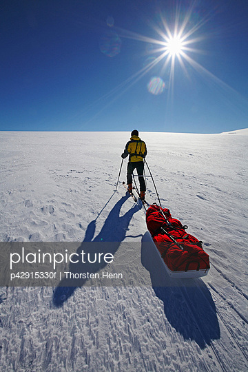 Man pulling pack in snow covered field