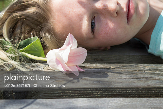 Girl lying down with flower